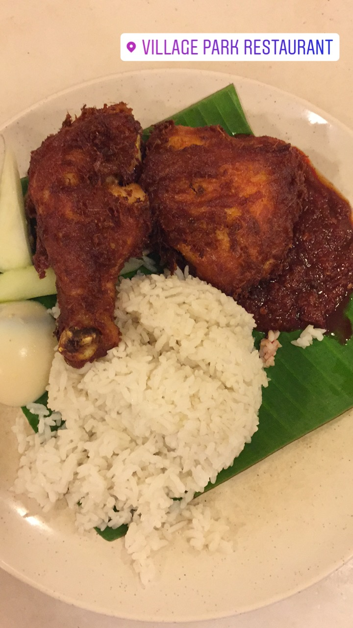Nasi lemak, white fragrant rice served with cucumber, hard boiled egg, ikan bilis, sambal and fried chicken